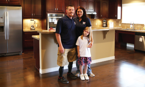 Marine PFC Isaac Blunt and Family in the kitchen of their accessible home provided by Homes For Our Troops